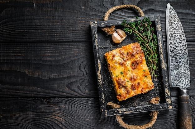 Porção de lasanha com carne picada de carne bovina e molho de tomate à bolonhesa em uma bandeja de madeira. fundo de madeira preto. vista do topo. copie o espaço.