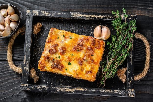 Porção de lasanha com carne picada de carne bovina e molho de tomate à bolonhesa em uma bandeja de madeira. fundo de madeira preto. vista do topo.