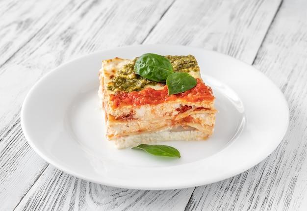 Porção de lasanha de ricota coberta com molho de tomate e pesto