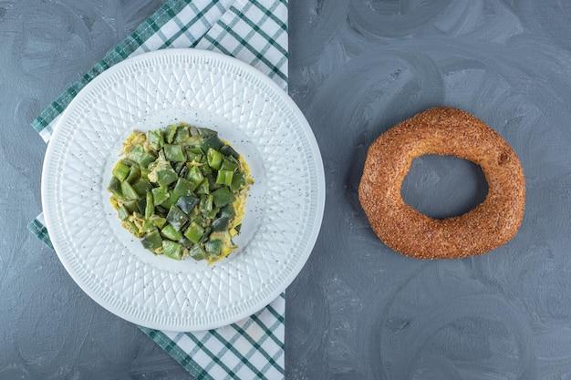 Porção de leguminosas de feijão cozida com ovos, ao lado de um bagel na mesa de mármore.