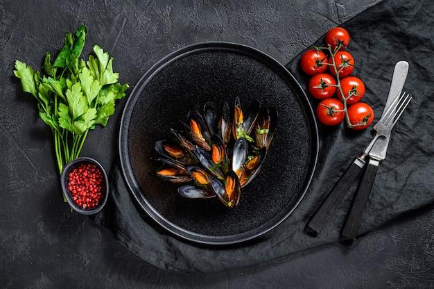 Porção de mexilhões deliciosos em molho de tomate e salsa. fundo preto. vista do topo