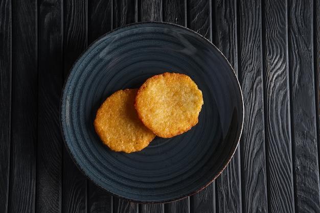 Porção de panquecas de batata frita na mesa de madeira escura