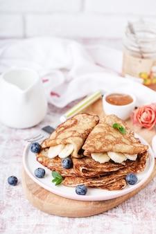 Porção de panquecas fritas com banana e mirtilos, em um prato, sobre uma tábua de madeira, em cima da mesa, mel, creme