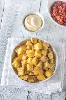 Porção de patatas bravas com molhos