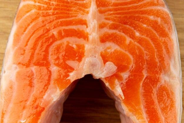 Porção de salmão vermelho cru cortado em fatias e colocado na superfície de madeira