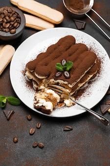 Porção de sobremesa de tiramisu clássico e biscoitos savoiardi no fundo de concreto