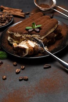 Porção de sobremesa tiramisu clássico em prato de cerâmica sobre fundo de concreto