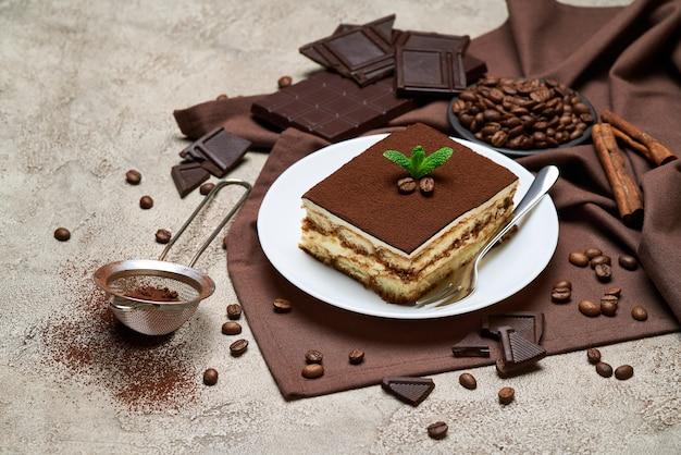 Porção de sobremesa tiramisu italiana tradicional e grãos de café na mesa de concreto cinza