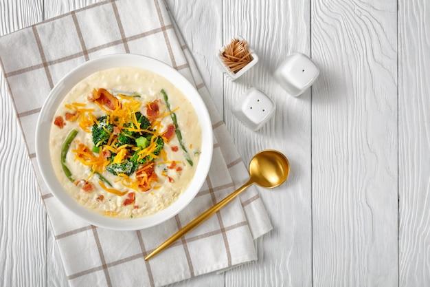 Porção de sopa de creme com brócolis, feijão verde, bacon frito e queijo cheddar ralado em uma tigela branca sobre uma mesa de madeira