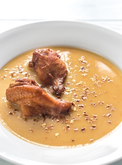 Porção de sopa de creme de ervilha com asas de frango defumado