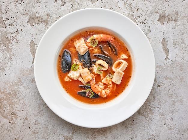 Porção de sopa de tomate com frutos do mar em prato branco vista de cima
