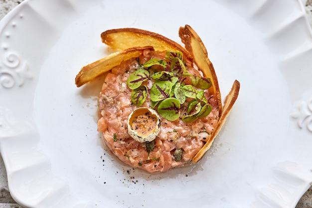 Porção de tártaro de salmão no prato branco, vista de cima