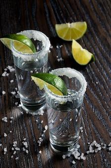Porção de tequila emoldurada por uma borda de sal com uma fatia de limão em copos altos