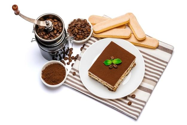 Porção quadrada de sobremesa tradicional italiana tiramisu em prato de cerâmica, moedor de café e biscoitos savoiardi um isolado