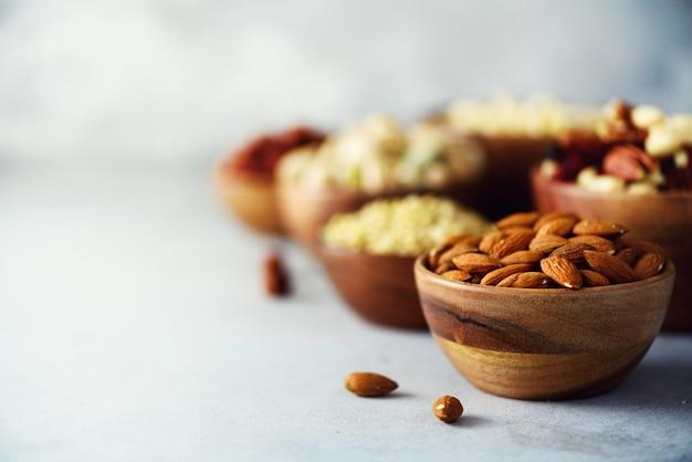 Porcas de amêndoa na tigela de madeira. variedade de nozes - castanha de caju, avelãs, amêndoas, nozes, pistache, nozes, pinhões, amendoim, passas