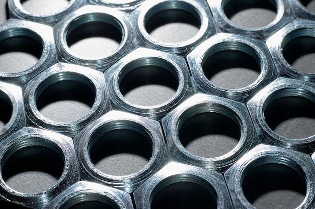 Porcas de metal cromadas de close-up na forma de favos de mel ficam próximas umas das outras formando uma área