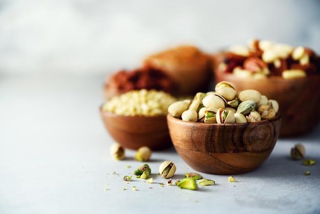 Porcas de pistache na bacia de madeira. variedade de nozes - castanha de caju, avelãs, amêndoas, nozes, pistache, nozes, pinhões, amendoim, passas