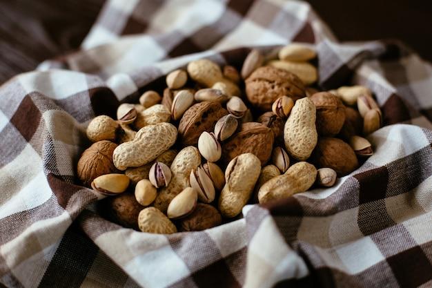 Porcas misturadas na toalha. grupo de nozes diferentes: amendoim, pistache, nozes. nozes orgânicas