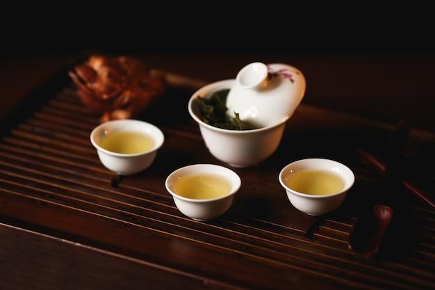 Porcelana gaiwan, três xícaras de chá chinês e dourado sapo na mesa de chá.