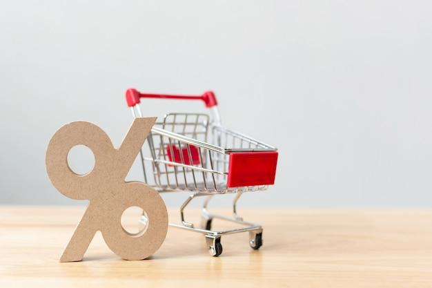 Porcentagem sinal símbolo ícone de madeira e carrinho de compras na mesa de madeira