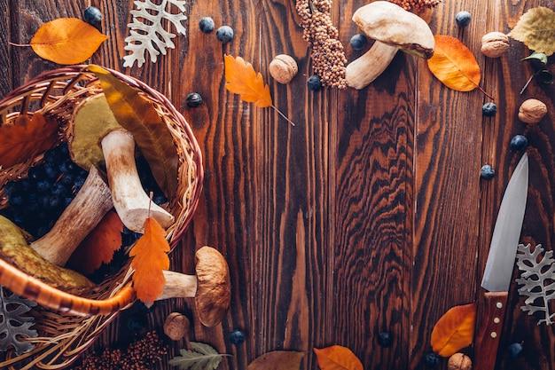 Porcini cresce rapidamente na cesta com bagas e nozes na mesa de madeira. colheita de outono. colheita de outono.