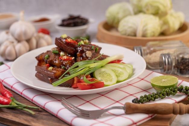 Porco doce em um prato branco com cebolinha picada, pimenta, limão, pepino, tomate e alho.