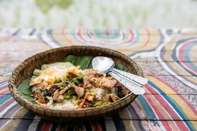 Porco e ovo de manjericão tailandês perto do campo de arroz