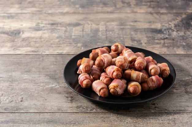 Porco em cobertores. salsichas embrulhadas em bacon defumado na mesa de madeira