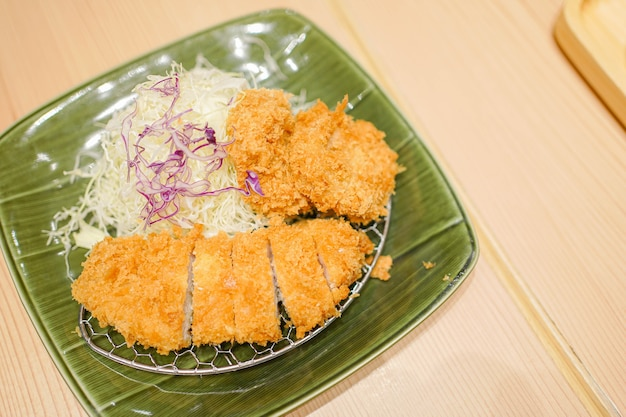 Porco empanado frito servido com molho, comida japonesa. Foto Premium