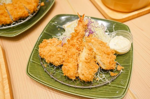 Porco empanado frito servido com molho, comida japonesa.