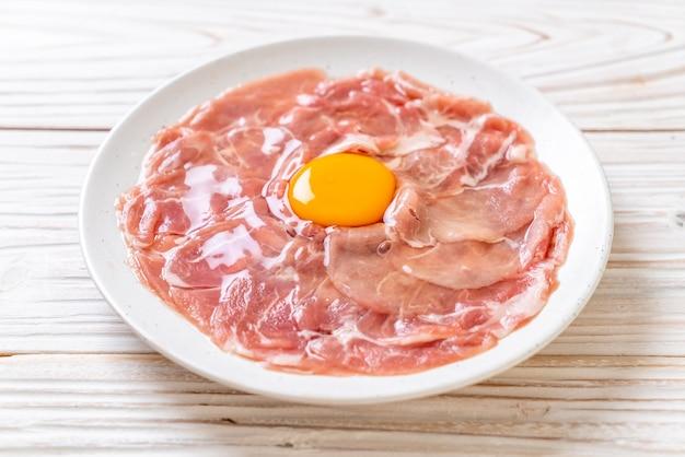 Porco fatiado fresco cru com ovo