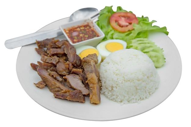 Porco frito com alho e arroz com ovo cozido com molho tailandês picante, foco seletivo.