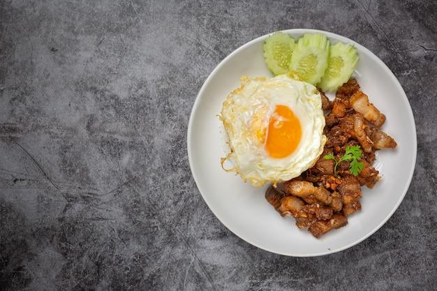 Porco frito com alho e pimenta servido com arroz e ovo frito