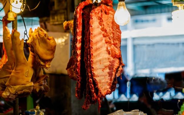 Porco pendurado no gabinete para venda no mercado local, tailândia