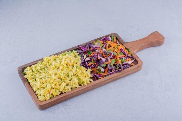 Porções de arroz integral e salada de repolho roxo em uma bandeja com fundo de mármore.