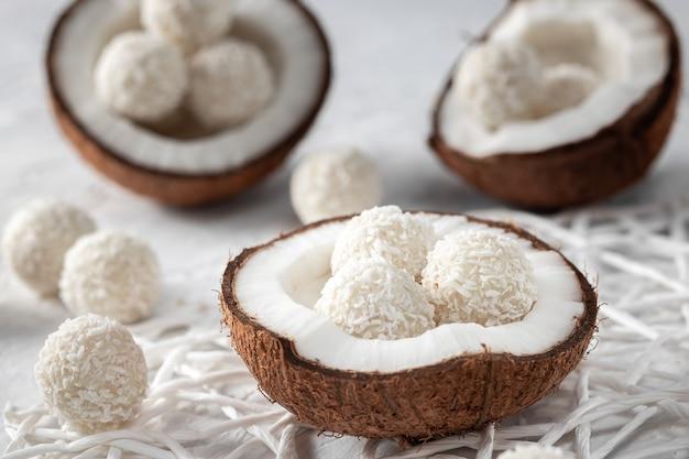 Porções de bolinhas de chocolate e coco branco na tigela, coco cru rachado, foco seletivo