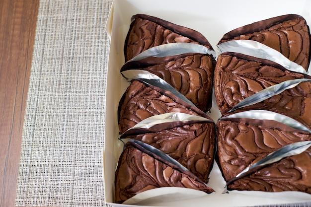 Porções de bolo de brownie de chocolate fresco na mesa de madeira