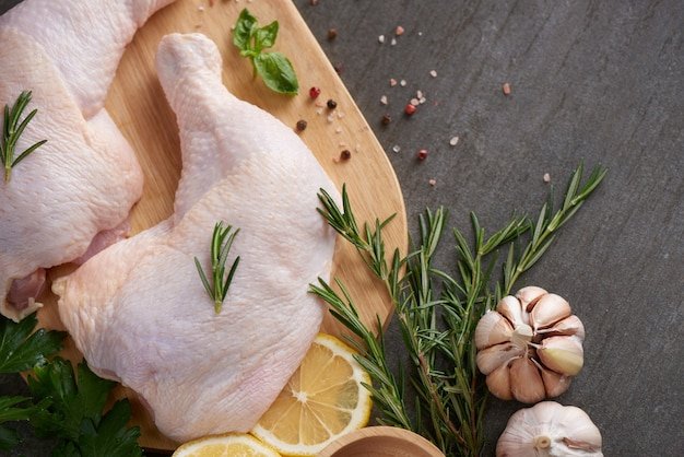 Porções de carne de frango fresca para cozinhar e grelhar com temperos frescos. coxa de frango cru cru na tábua.