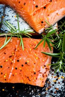 Porções de filés de salmão cru fresco com ervas aromáticas e azeite