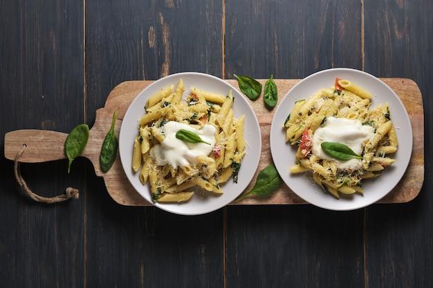 Porções de macarrão com molho de tomate, espinafre, parmesão e bolonhesa em uma tábua de madeira de cozinha grande.