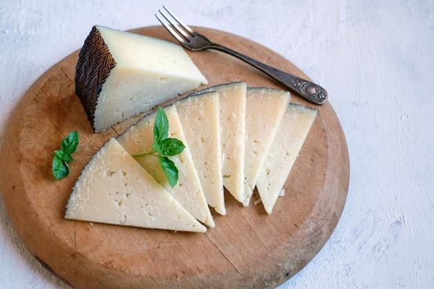 Porções de queijo espanhol manchego curado na tábua