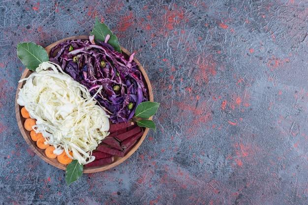 Porções de repolho vermelho e branco picado, beterraba e cenoura em uma bandeja na mesa preta.