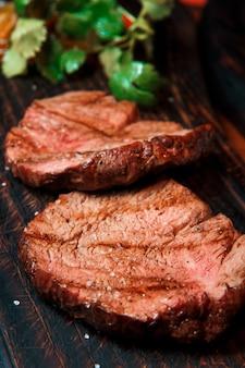 Porções grossas e suculentas de bife de filé frito são servidas polvilhadas com sal em uma velha tábua de madeira o prato está pronto para servir