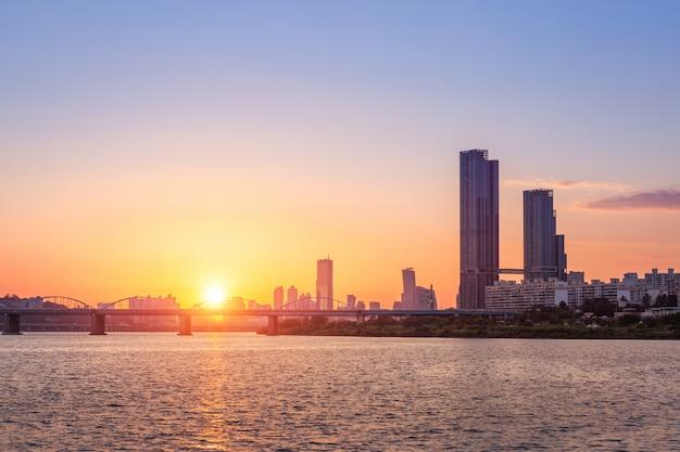 Pores do sol atrás dos arranha-céus de yeouido e pontes do outro lado do rio han, no centro de seul, na coréia do sul.