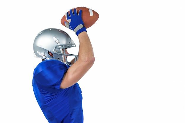 Porfile vista do jogador de futebol americano, pegando a bola