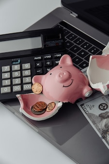 Porquinho quebrado, calculadora e notas de dólar no teclado. conceito de finanças e falência. imagem vertical.