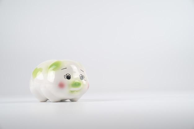 Porquinho verde e rosa branco triste na frente do fundo branco.