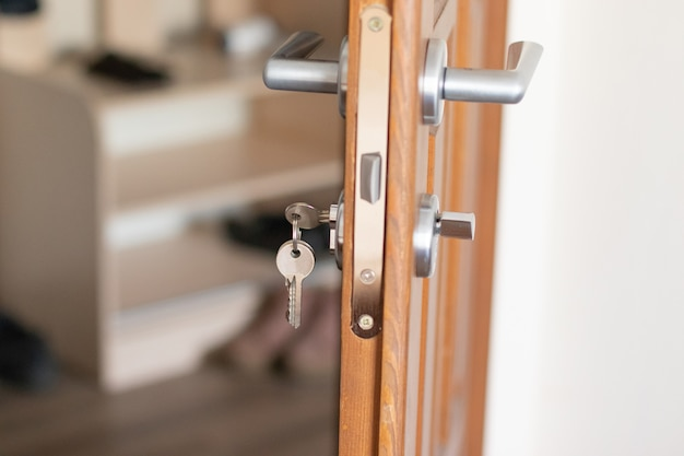 Porta aberta com chaves, chave no buraco da fechadura, trava closeup