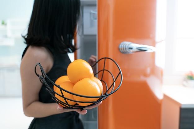 Porta aberta do refrigerador da mulher na cozinha. laranja na mão.