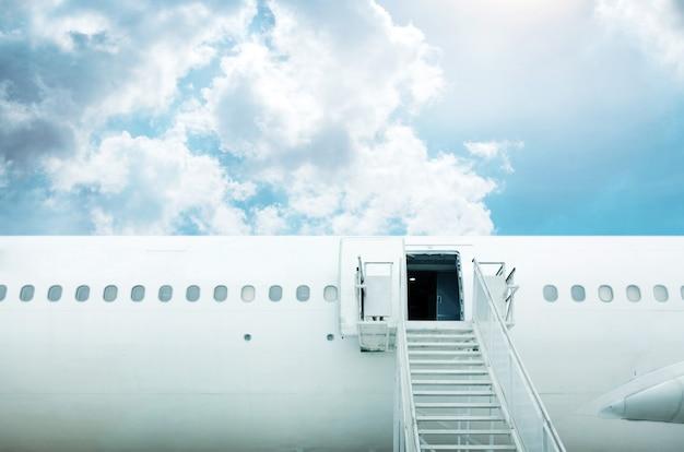 Porta aberta e escada de avião com céu azul para viagens de luxo em segundo plano